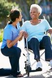 Personale che dispensa le cure che spinge donna maggiore in sedia a rotelle fotografie stock libere da diritti