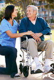 Personale che dispensa le cure che spinge uomo maggiore in sedia a rotelle Immagine Stock Libera da Diritti