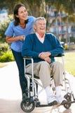 Personale che dispensa le cure che spinge uomo maggiore in sedia a rotelle Fotografia Stock