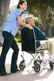 Personale che dispensa le cure che spinge uomo maggiore in sedia a rotelle Immagini Stock Libere da Diritti