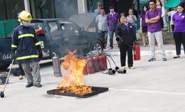 Personale che pratica un'esercitazione antincendio che mette fuori un fuoco con un tipo estintore della polvere Fotografia Stock
