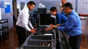 Personale di sicurezza maschio che assiste i pendolari con il loro bagaglio stock footage