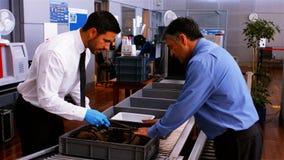 Personale di sicurezza maschio che per mezzo del metal detector video d archivio