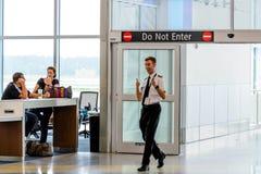 Personale di volo che dà i pollici su che entrano nel portone di imbarco Immagine Stock