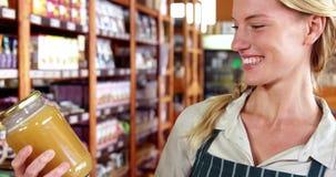 Personale femminile che guarda un barattolo di miele in supermercato archivi video