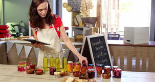Personale femminile che sistema le olive, le prerogative e olio d'oliva sul contatore video d archivio