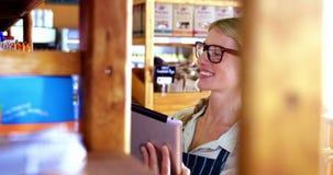 Personale femminile che utilizza compressa digitale nel supermercato stock footage