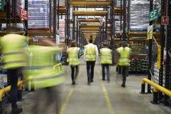 Personale in maglie riflettenti che cammina in un magazzino, vista posteriore Fotografia Stock