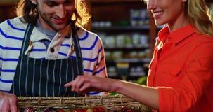 Personale maschile che assiste donna nella selezione degli ortaggi freschi archivi video