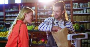 Personale maschile che assiste donna nella selezione delle verdure stock footage