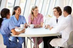 Personale medico che chiacchiera nella mensa moderna dell'ospedale Fotografia Stock