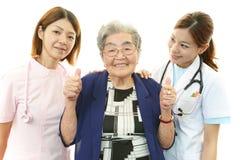 Personale medico sorridente con la donna anziana Immagini Stock Libere da Diritti