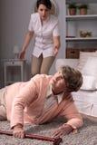 Personale sanitario che aiuta donna anziana danneggiata immagine stock