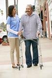 Personale sanitario che aiuta uomo senior ad usare struttura di camminata immagine stock libera da diritti