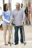 Personale sanitario che aiuta uomo senior ad usare struttura di camminata fotografie stock