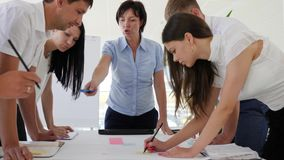 Personalen föreslår idénäringslivsutveckling bredvid skrivbordet i konferensrum arkivfilmer