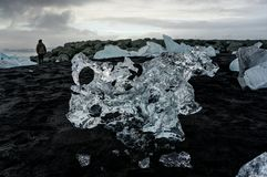 Personanseende på den svarta stranden med isberg som svävar i Jokulsa arkivfoton