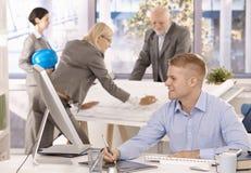 Personas alegres del arquitecto en oficina Imágenes de archivo libres de regalías