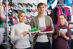 3 personas con los zapatos en la tienda del deporte Fotos de archivo libres de regalías