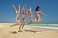 Personas de los amigos que saltan en la playa Imágenes de archivo libres de regalías