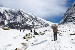 Personas de trekkers y de porteros en las montañas de Himalaya Foto de archivo libre de regalías