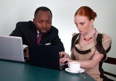 Personas del asunto con las computadoras portátiles en el escritorio de oficina Imagen de archivo