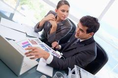 Personas del asunto que estudian estadísticas con una computadora portátil Imagen de archivo