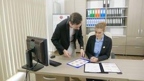 Personas del negocio en una oficina del escritorio que hablan y que analizan cartas financieras metrajes
