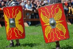 Personas en los trajes históricos que sostienen los escudos rojos Foto de archivo libre de regalías