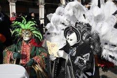 Personas enmascaradas en traje colorido con el plumaje que se sienta en café Fotos de archivo libres de regalías