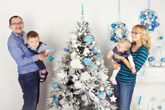 Personas felices de la familia de cuatro miembros que adornan el árbol de navidad Foto de archivo libre de regalías