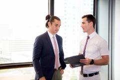 Personas jovenes americanas del hombre de negocios dos que sostienen el tablero y que discuten el trabajo en la sala de reunión Foto de archivo libre de regalías