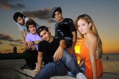 Personas jovenes diversas que presentan en la puesta del sol Fotografía de archivo