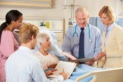 Personas médicas que visitan al paciente femenino mayor en cama Fotografía de archivo libre de regalías