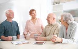 Personas mayores que pasan el tiempo junto en la tabla foto de archivo libre de regalías