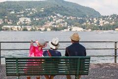 3 personas que miran y que indican el lago del como Foto de archivo