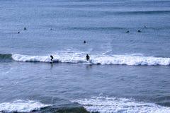 Personas que practica surf azules profundas de Océano Atlántico Foto de archivo libre de regalías
