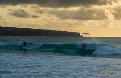 Personas que practica surf que cogen la onda fotos de archivo
