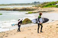 Personas que practica surf con el tablero que practica surf Imagen de archivo libre de regalías