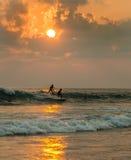 Personas que practica surf contra fondo de la puesta del sol del océano Foto de archivo libre de regalías