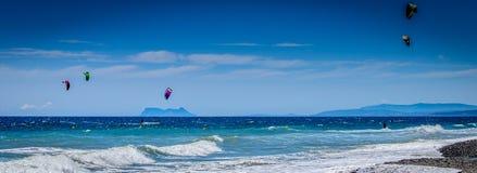 Personas que practica surf de la cometa en la playa de Guadalmansa Imágenes de archivo libres de regalías