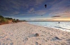 Personas que practica surf de la cometa en la puesta del sol en la playa de plata, bahía Australia de la botánica fotos de archivo
