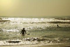 Personas que practica surf de la madrugada Imagenes de archivo