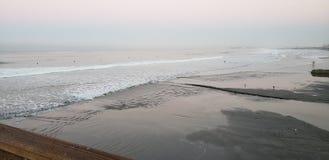 Personas que practica surf de la playa de la costa en la acción imagenes de archivo