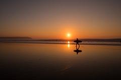 Personas que practica surf de la puesta del sol Fotos de archivo libres de regalías