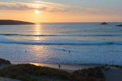 Personas que practica surf de la puesta del sol de Cornualles que practican surf la bahía y la playa Cornualles del norte Inglate Fotos de archivo libres de regalías