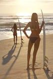 Personas que practica surf de las mujeres en playa del bikiní y de la puesta del sol de las tablas hawaianas Imagen de archivo