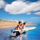 Personas que practica surf de los muchachos que practican surf el salto de funcionamiento en las tablas hawaianas Fotografía de archivo