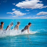 Personas que practica surf de los muchachos que practican surf el salto de funcionamiento en las tablas hawaianas Imágenes de archivo libres de regalías