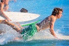 Personas que practica surf de los muchachos que practican surf el salto de funcionamiento en las tablas hawaianas fotos de archivo